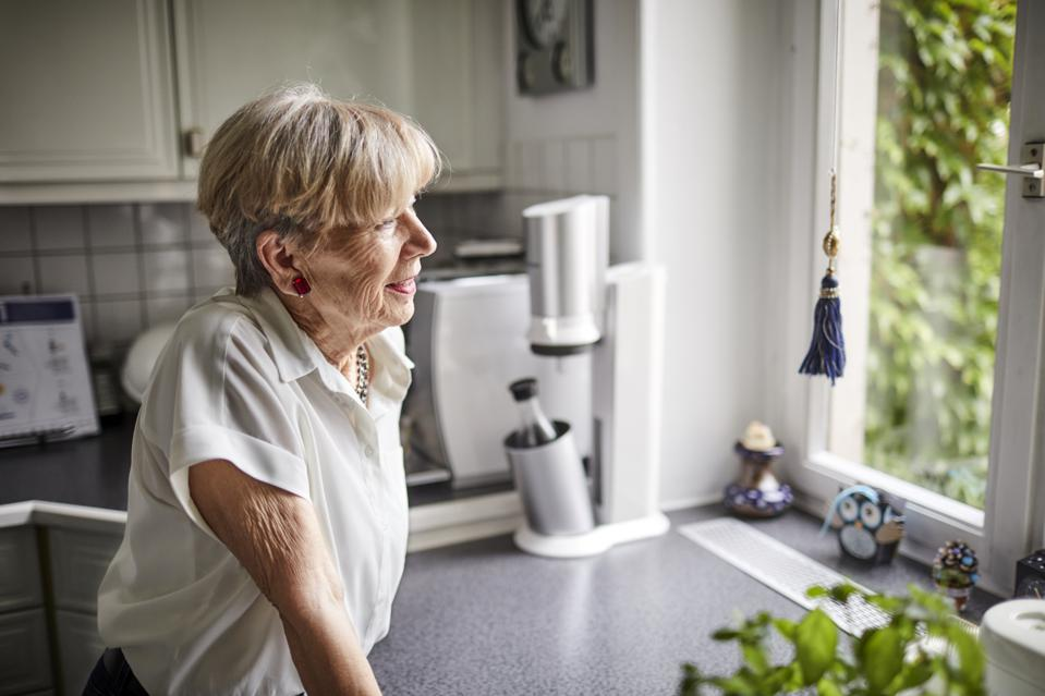 Smiling senior woman in kitchen at home looking out of window