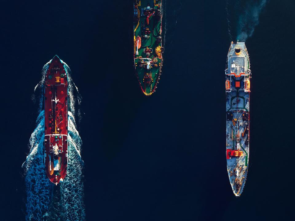 Aerial top view of a busy harbour. Large commercial ships cruising in the port
