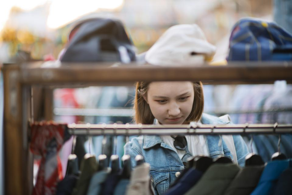 Young girl choosing clothes in a second hand market in summer, zero waste concept
