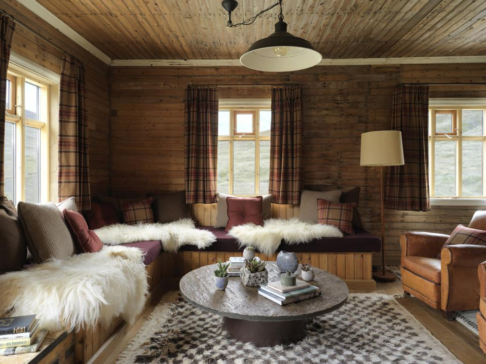 A rustic living room with fur throws, leather furniture and wood beam walls and ceiling.