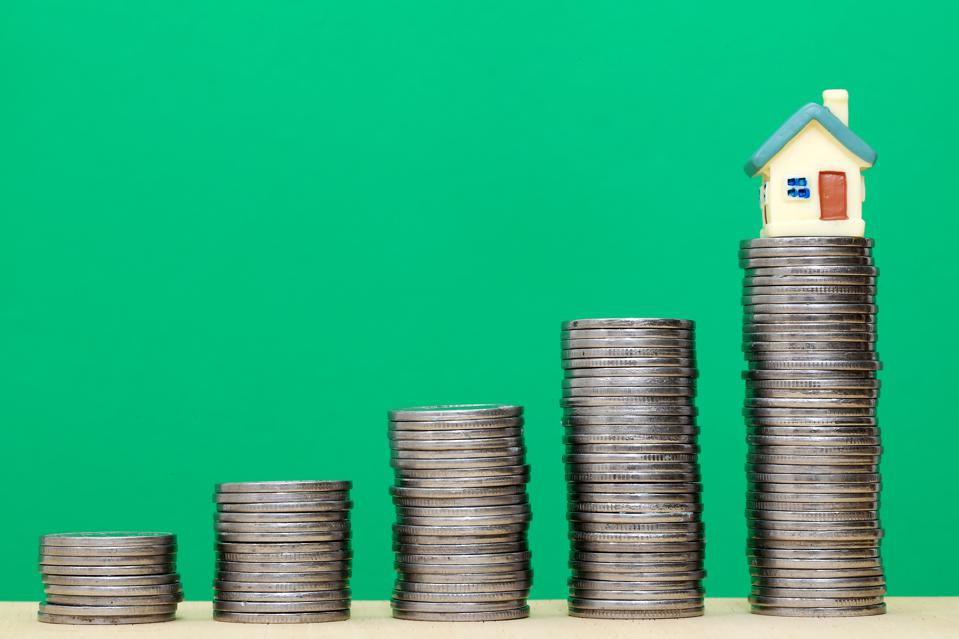 Stack of coins and miniature house against green