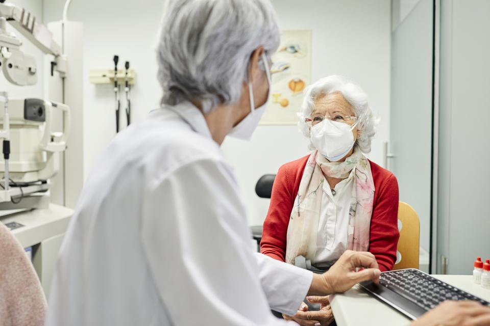 Doctor discussing with aged woman in hospital