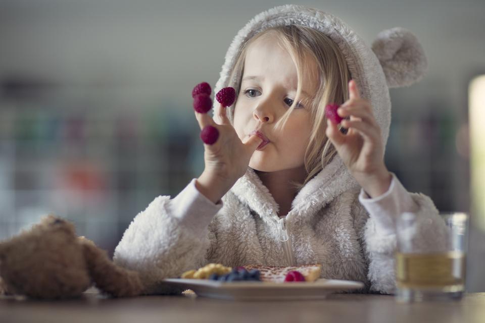Girl in cozy hooded pyjamas, eating raspberries off her fingers