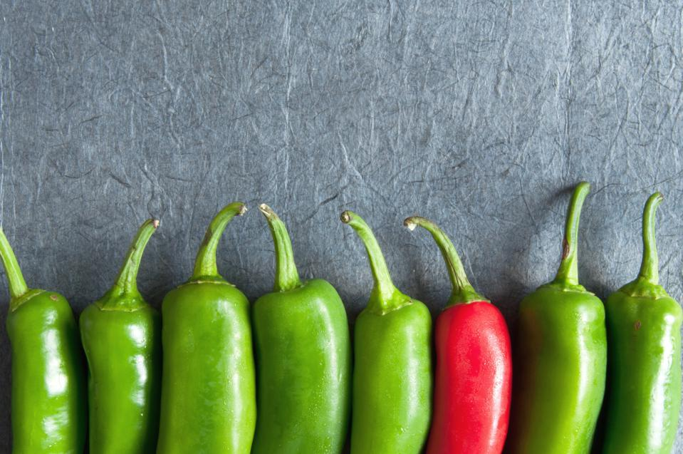 Green chili peppers with one red showing importance of personal branding.