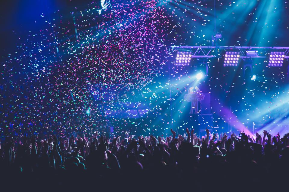 A crowded concert hall with scene stage lights, rock show performance, with people silhouette, colourful confetti explosion fired on dance floor air during a concert festival