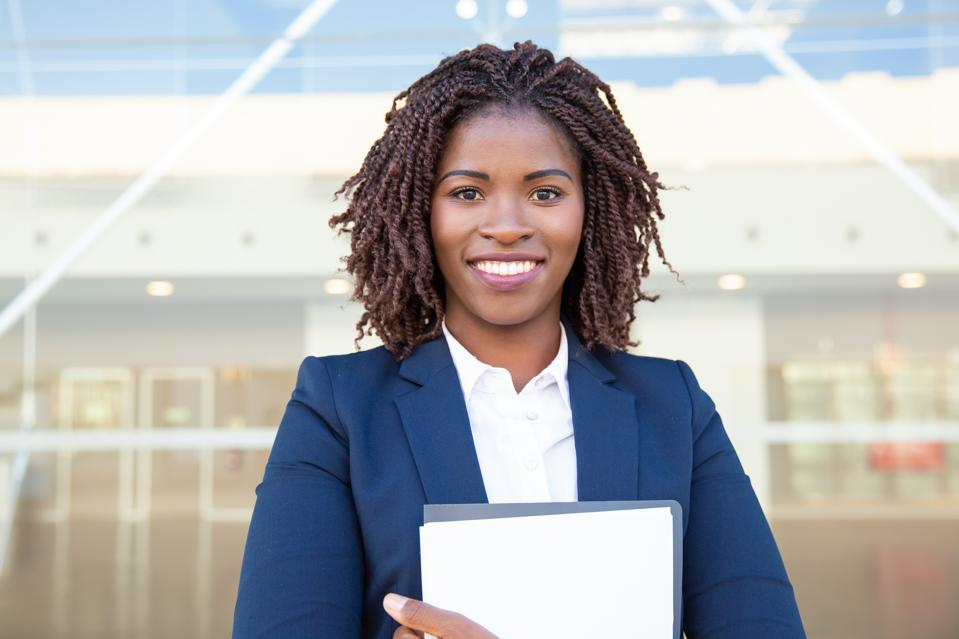 Happy young businesswoman holding folder