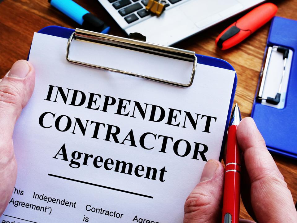Man is signing Independent contractor agreement by pen.