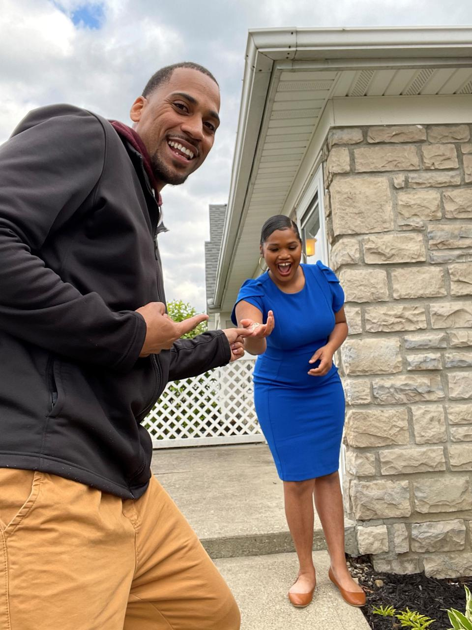 Harlem Globetrotter and Ohio real estate agent Julian ″Zeus″ McClurkin hands 19-year-old Chloe Green the keys to the two-bedroom condominium she purchased.