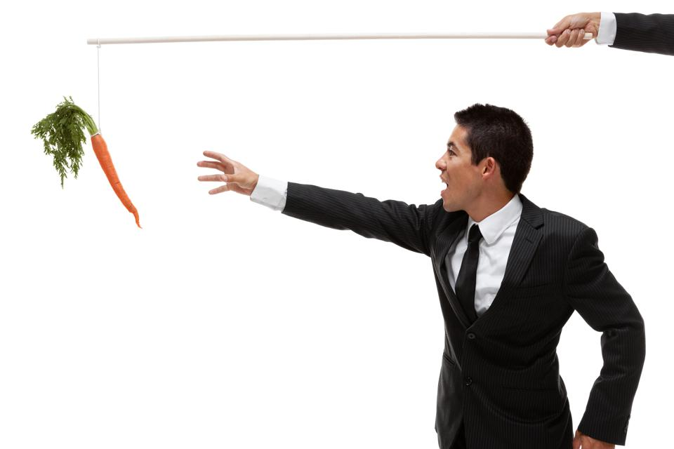 Businessman reaching for carrot on a stick