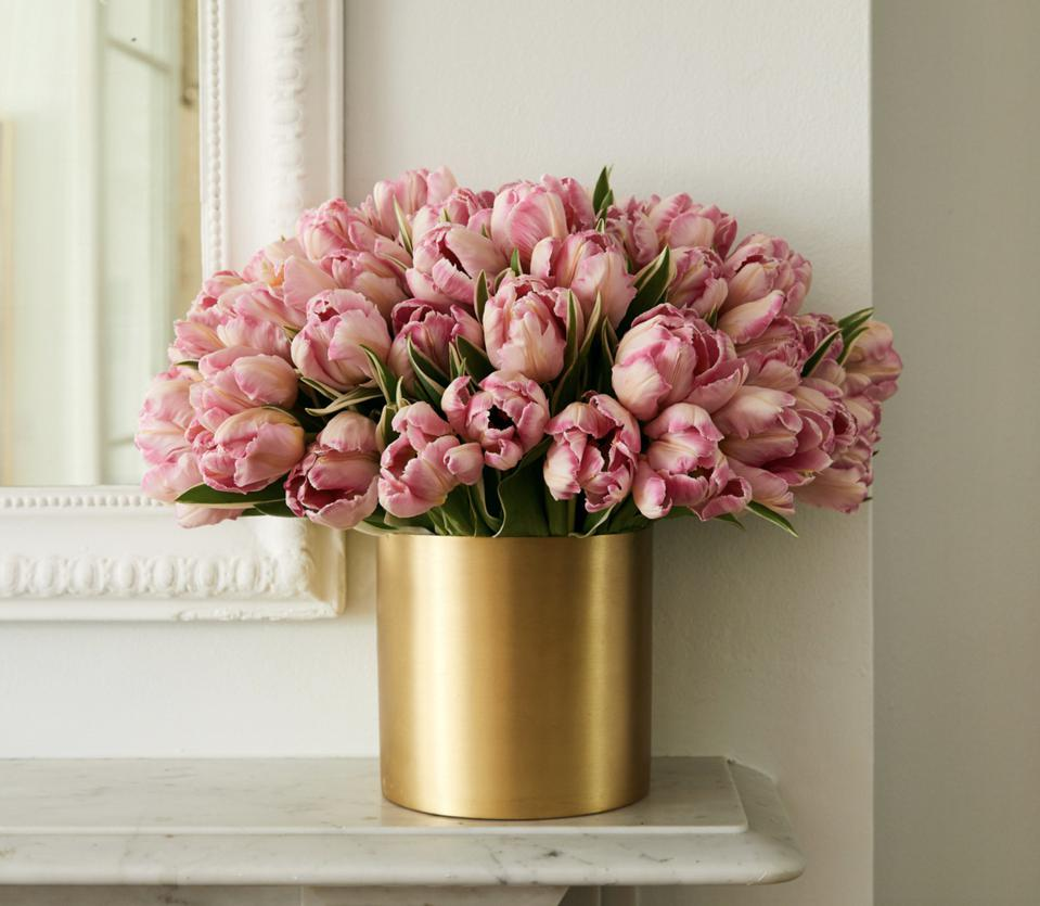 a bunch of pink tulips in brass gold vase
