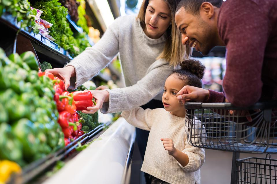 Mixed race couple grocery shopping with their preschool-age daughter