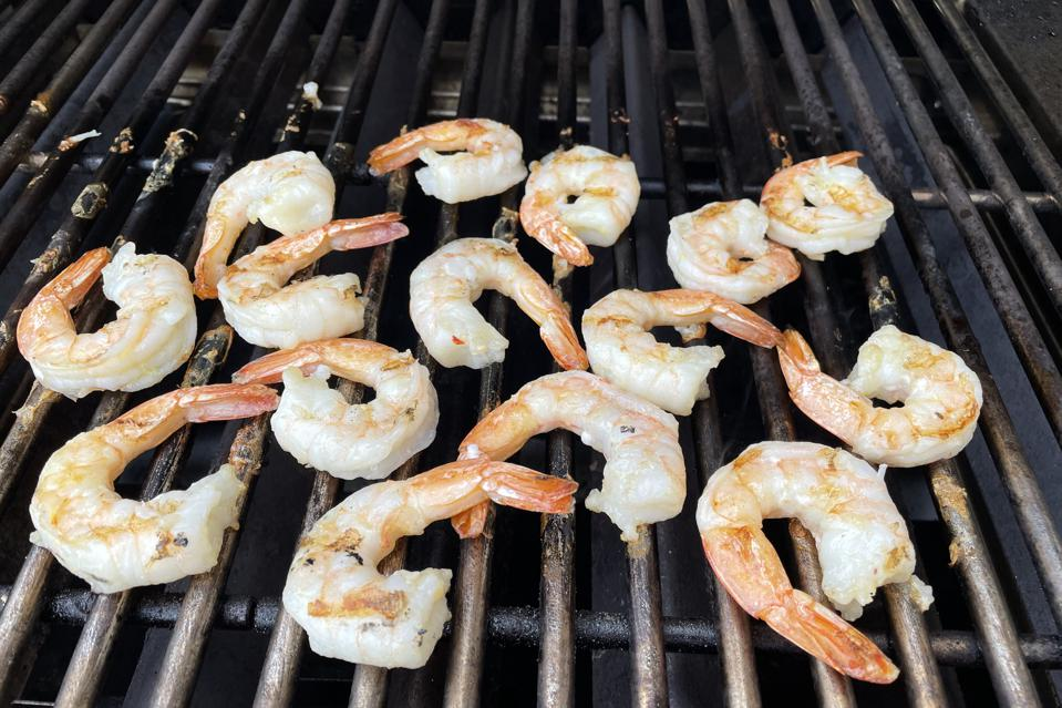 Perfectly grilled Colossal shrimp are shown on a stainless-steel grill grate just before they are removed and placed in a tomatillo salsa marinade.