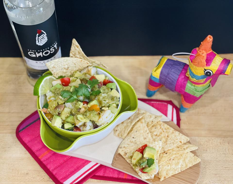 A bowl of grilled shrimp ceviche is shown in a bowl with a garnish of fresh lime, cilantro and tortilla chips.  In the background is a colorful miniature piñata and a bottle of Ghost Tequila.