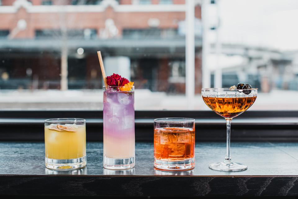 A line up of cocktails, including a purple one, with Coors Field in the background