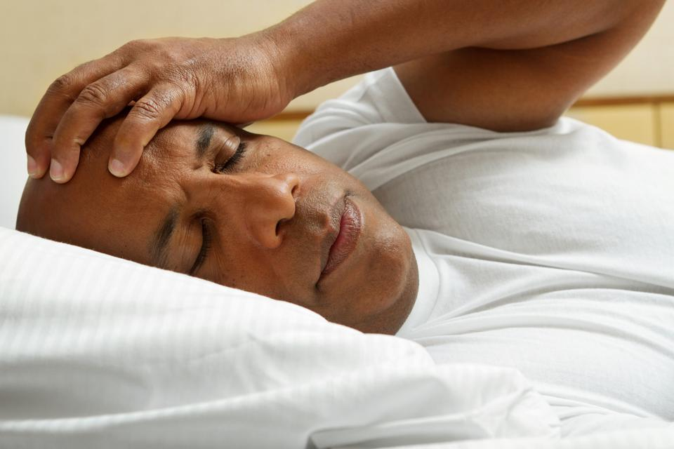 Black man sleeping in bed with Insomnia
