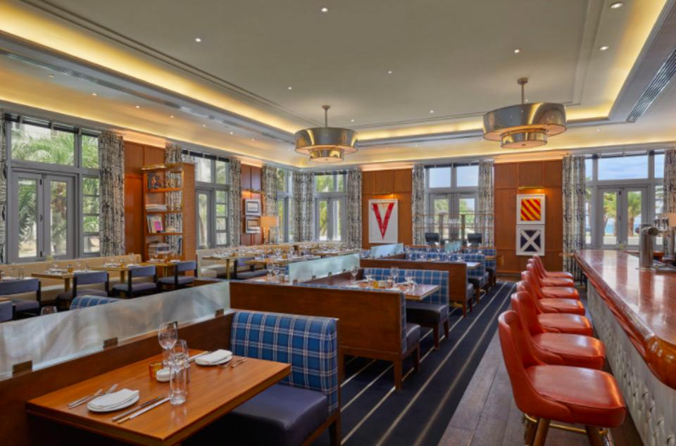 the inside of an elegant seafood restaurant with plaid booths and leather bar stools