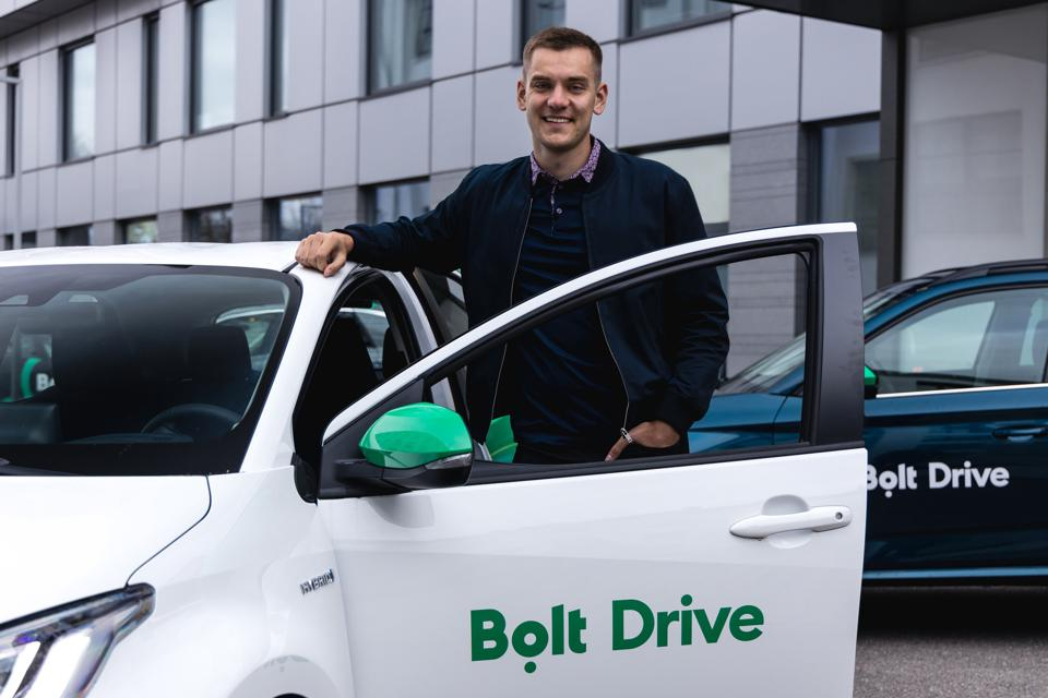 Chief executive of Bolt standing beside a car in the coming's Bolt Drive service.