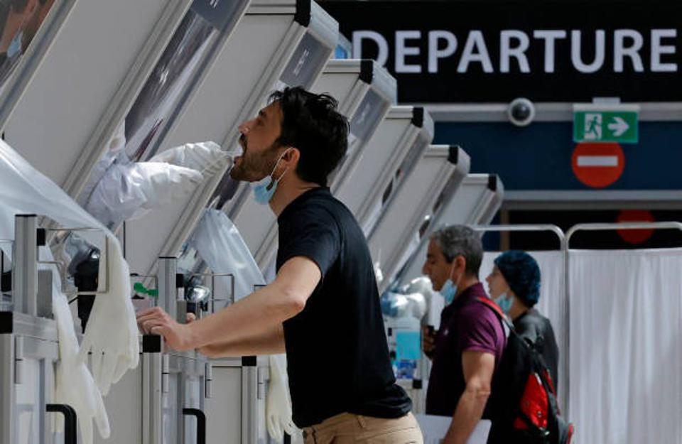 A medic collects a swab sample from a traveller at a rapid COVID-19 testing booth in Israel's Ben Gurion Airport, near Tel Aviv, on April 6, 2021.