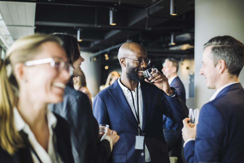 Smiling entrepreneur drinking black coffee while standing with colleagues in office