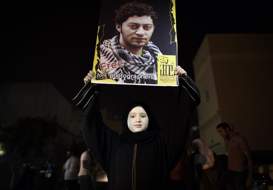 A Bahraini girl holds up a portrait of jailed Bahraini photographer Ahmed Humaidan.