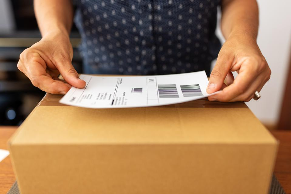 Woman preparing package for online delivery