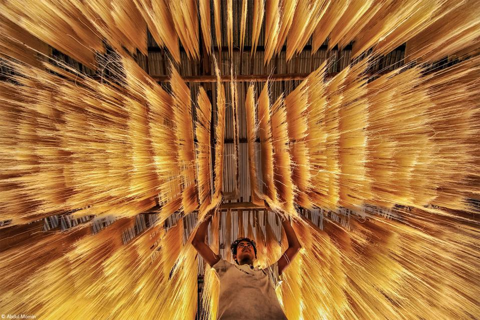 Food Photo Competition: a worker inspecting if rice noodles got dried rightly.
