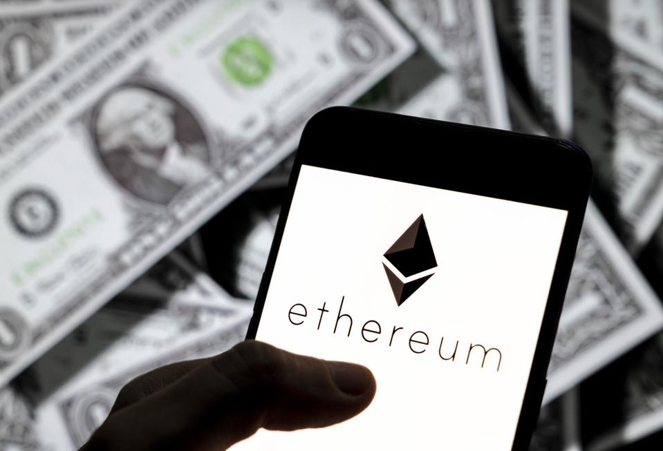 In this photo illustration, cryptocurrency ether, is displayed along with some dollars.