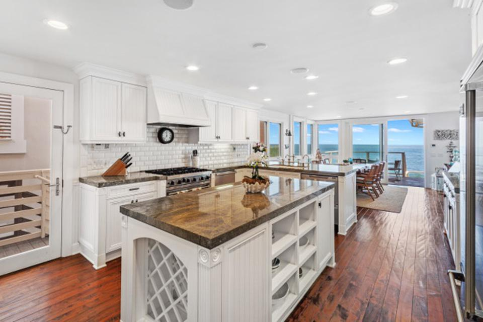 A large, modern white kitchen overlooking the water