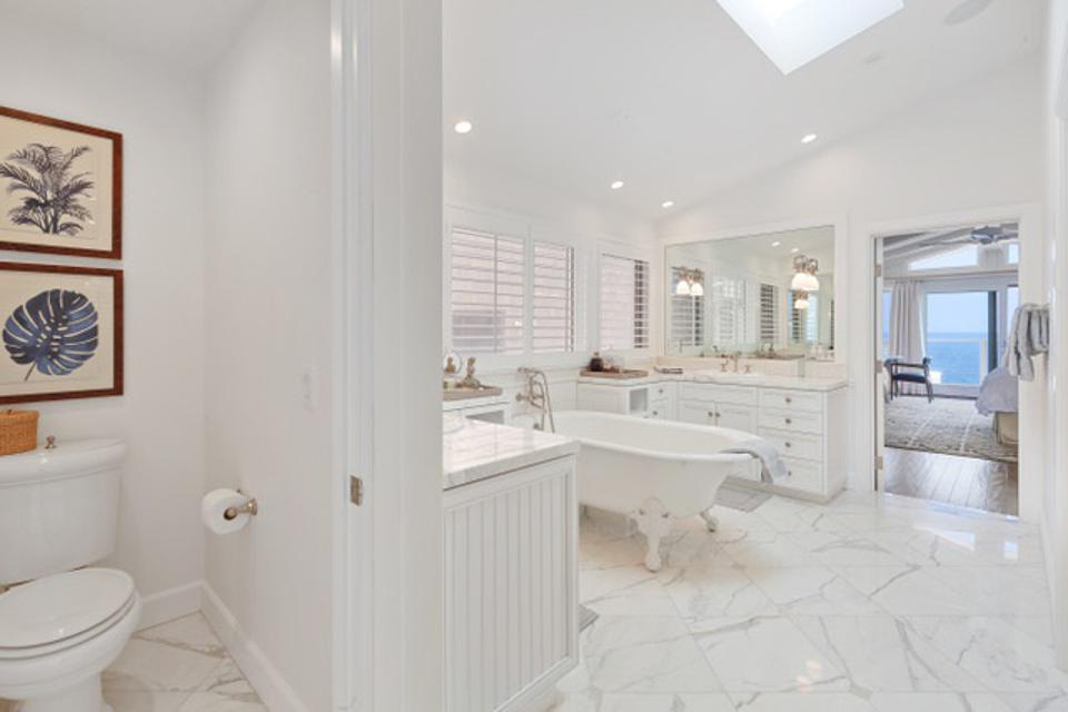 Large, white, marble and stone primary bath