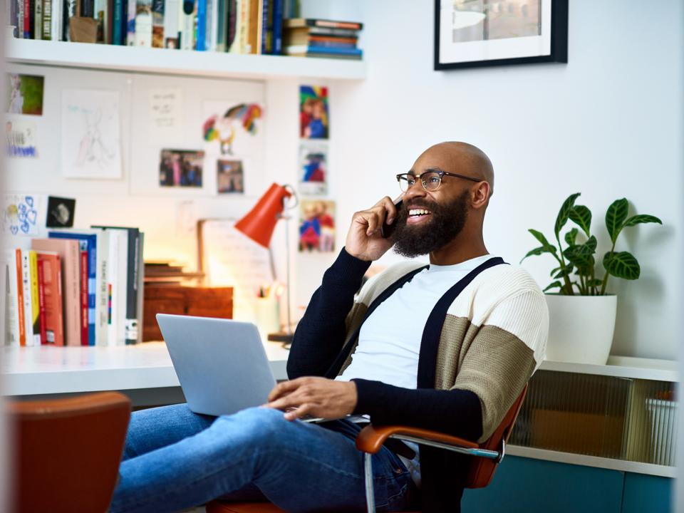 FlexJobs deal: Cheerful businessman working from home on phone