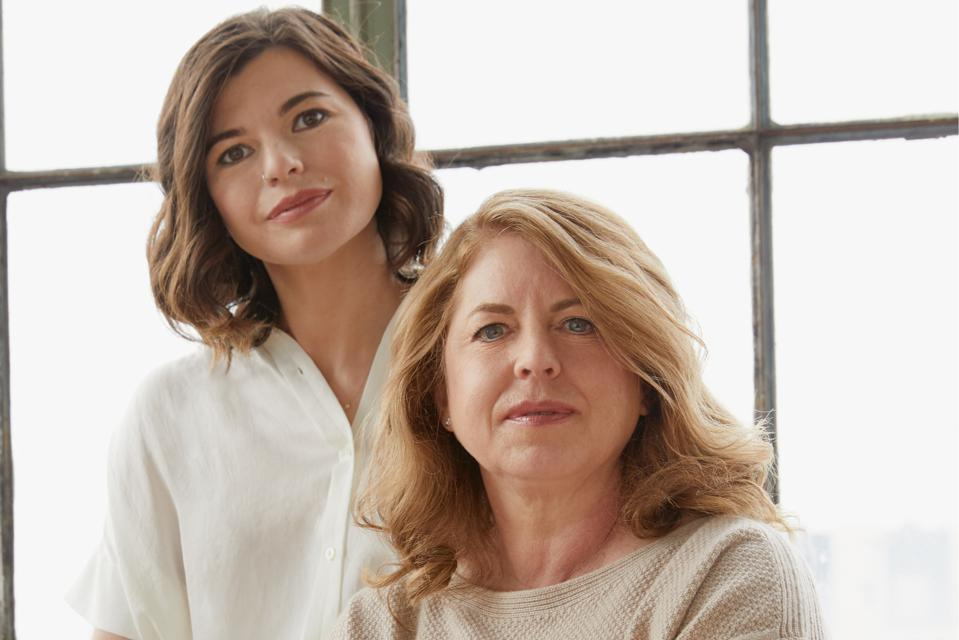 Adult daughter and her mother standing in front of a window and looking at the camera