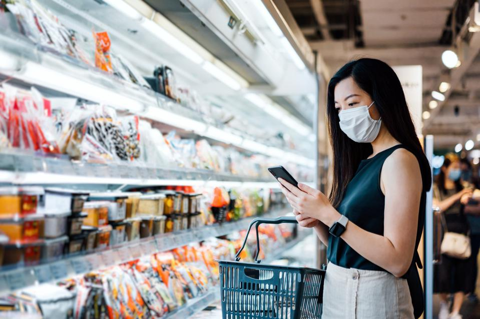 Young Asian woman with protective face mask holding shopping basket and using smartphone while grocery shopping in a supermarket