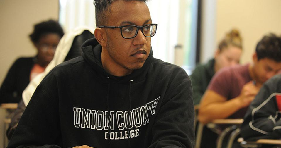 Student with glasses and UCC sweatshirt looking to the right from his desk.