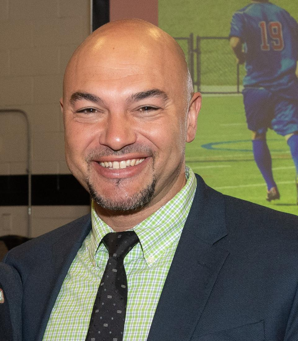 Bald headed man smiling into camera while wearing suit and tie, seen from chest up.