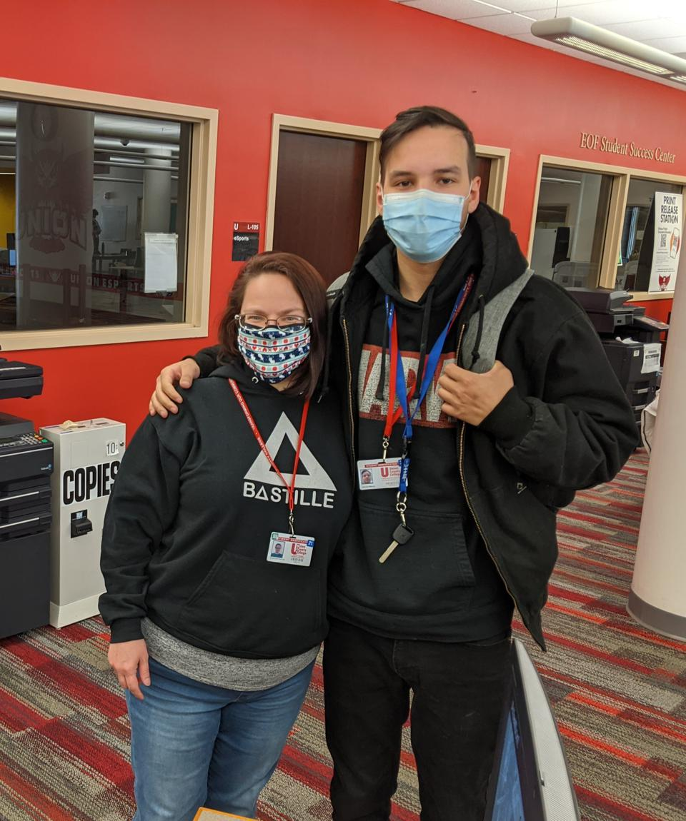 Masked mother and teenage son standing in college library.