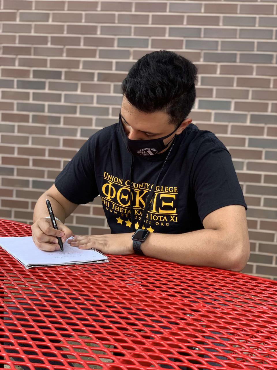 Masked UCC student in a t-shirt writing with a pen and notebook.