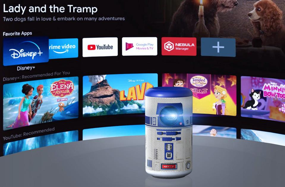 Nebula Capsule II R2-D2 projector in from of a a screen showing  Google Android TV 9