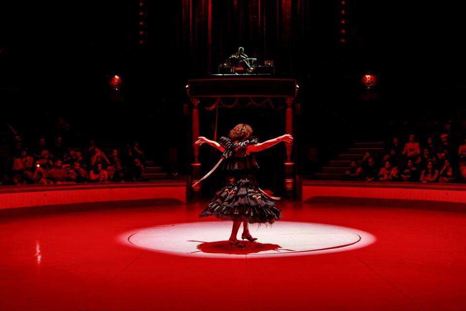 Une femme dans une robe de style flamenco sous les projecteurs sur une scène de cirque ronde rouge