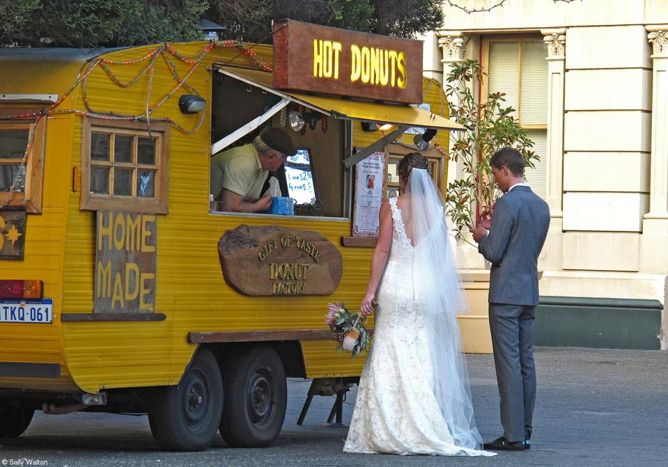A bride and groom  eating at a Hot Donuts food truck.