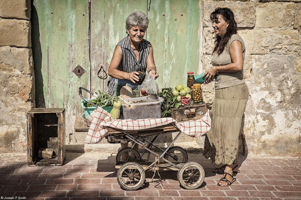 A woman sells capers from an old pram in Malta.