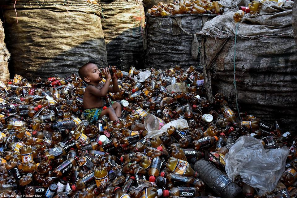 A little child drinking from a bottle at a garbage dump.