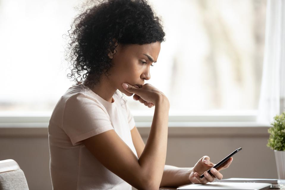Pensive woman looking at stock market data on smart phone