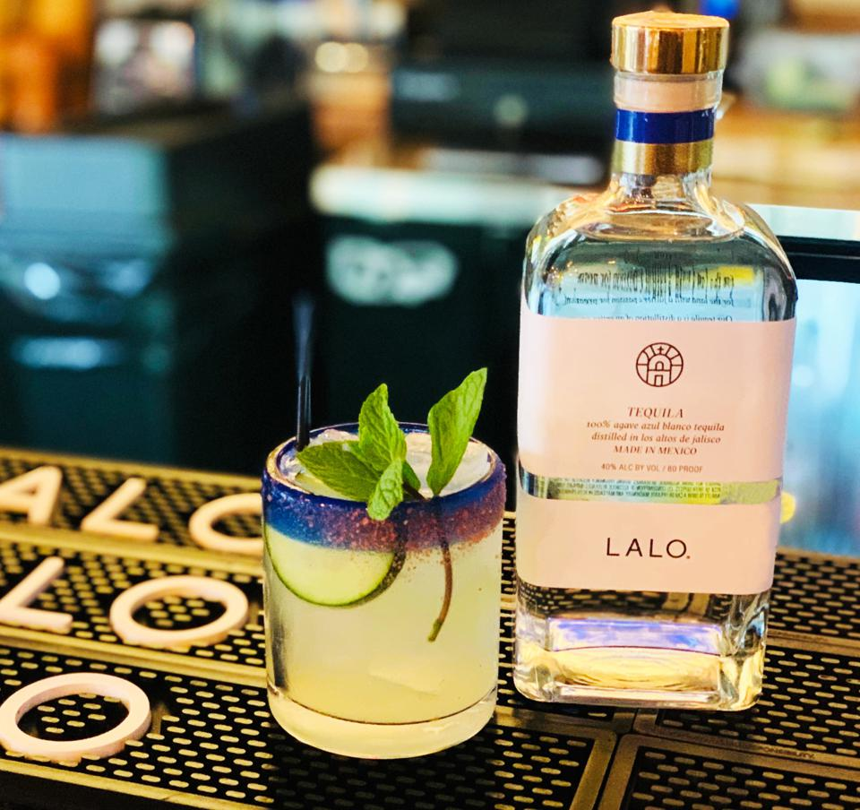Bottle of LALO tequila with a cocktail on a bartop.