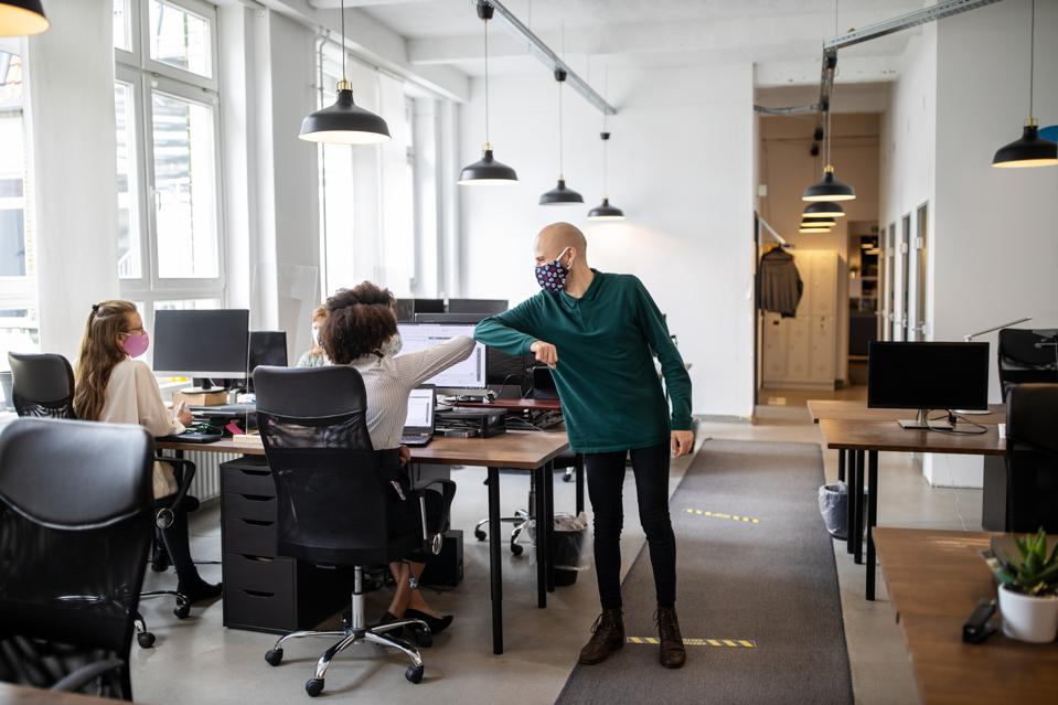Colleagues greeting with elbow bump in office