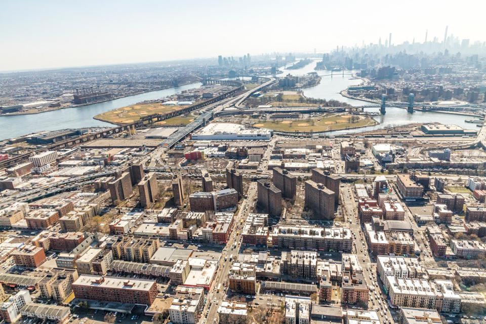 Aeriel view of multifamily buildings in the outer boroughs with Manhattan in the distance