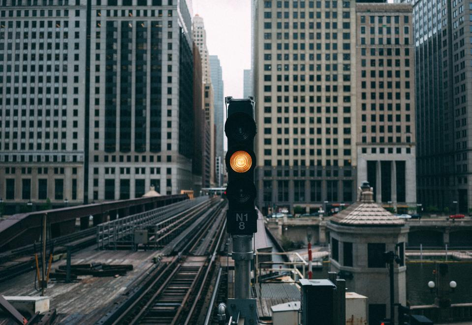 Yellow railway traffic light on elevated train track in Chicago, Illinois.