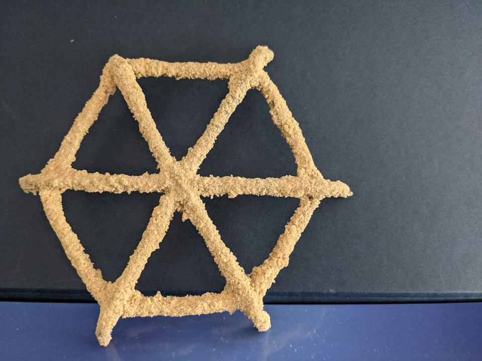 Against a blue background is a yellow-sand covered reef star. It is hexagon-shaped with the ″spokes″ of the star protruding out form the edges of the hexagon.