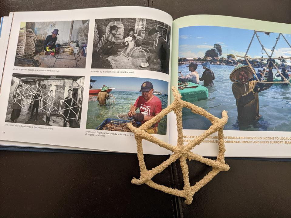 A book sits open with five photographs of Indonesian people working to create the reef stars. They include a man painting a steel frame, several people pouring sand over one, several people holding completed reef stars, a man standing in the ocean attaching a coral fragment, and a smiling man standing in the ocean holding up a seeded reef star ready to be planted and secured to the ocean floor. A model of a reef star sits on top of the open book.