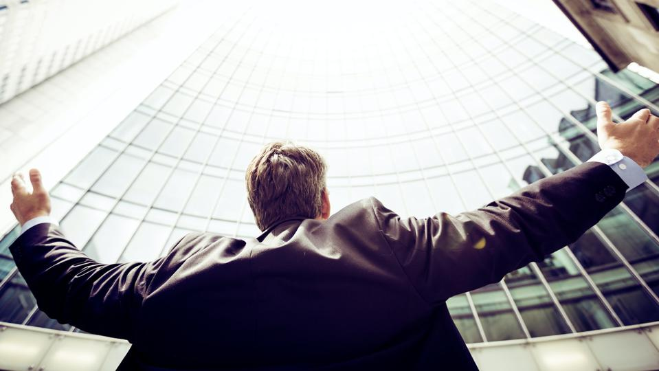 Man with his arms out and his back to camera looking up at a tall office building.