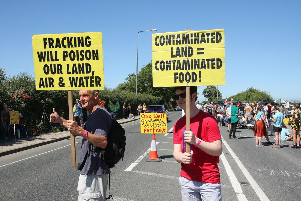 Two local Anti Frack Protesters hold placards on a main road...